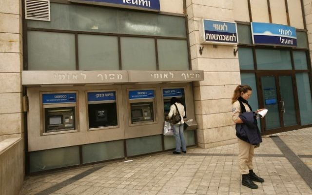 Des Israéliens retirent de l'argent aux distributeurs de la banque Leumi à Jérusalem (Crédit : Miriam Alster/Flash90)