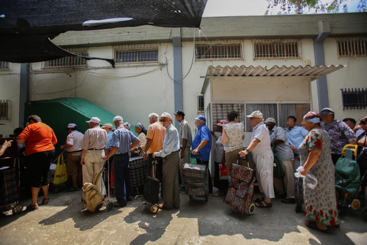 People waiting in line for food packages at a distribution center for needy in Lod on September 11, 2012. (photo credit: Yonatan Sindel / Flash90)