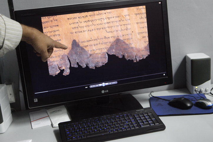 An Israel Antiquities Authority worker points to a spectral image photograph of fragments of the Dead Sea scrolls, at the Israel Museum in Jerusalem on Wednesday, December 18 (photo credit: Miriam Alster/Flash90)