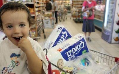 """Un jeune """"client"""" à la caisse d'un supermarché israélien (Crédit : Nati Shohat/Flash90)"""