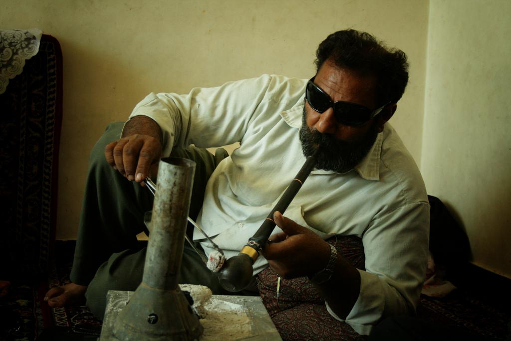 An Iranian man smoking opium in Kerman, Iran. (photo credit: CC BY-SA hypertornado, Flickr)