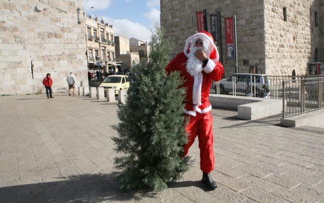 Un homme habillé en Père Noël avec un sapin de Noël, porte de Jaffa, devant la Vieille Ville de Jérusalem, en décembre 2008. Illustration. (Crédit : Yossi Zamir/Flash90)