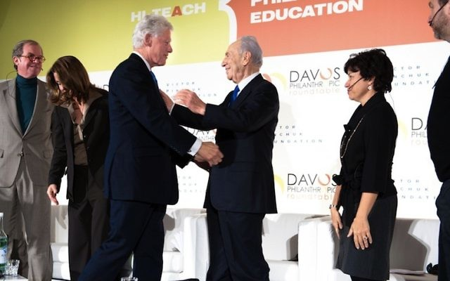 Shimon Peres, alors président, échange une poignée de mains avec l'ancien président américain Bill Clinton, lors d'un meeting au Forum économique mondial de Davos, en Suisse, en 2010. (Crédit : Sergei Illin/Flash90)