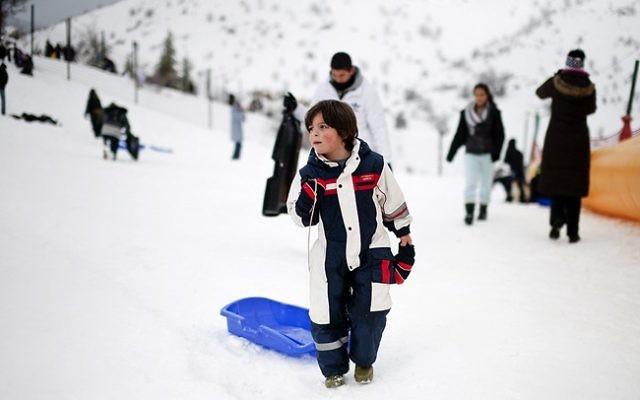 Des enfants faisant de la luge à la station de ski du mont Hermon (Crédit : Dima Vazinovich/Flash90)