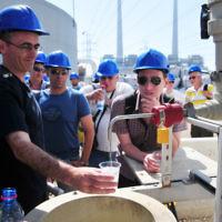 Des visiteurs remplissent leurs verres avec de l'eau traitée dans une usine de dessalement située aux abords de Hadera (Crédit : Shay Levy/Flash90)