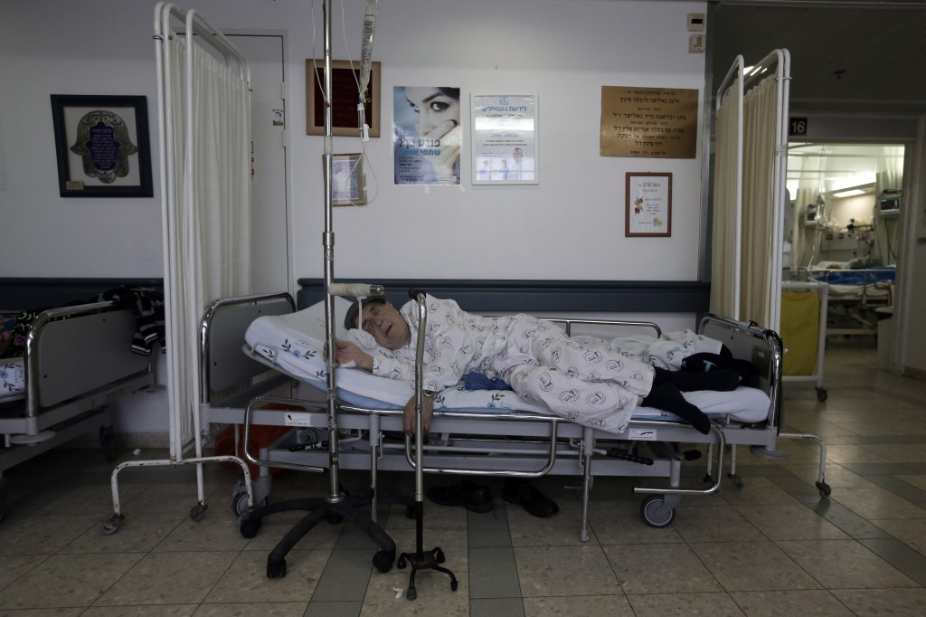 Overcrowding at hospitals has forced many patients to lie on beds in the corridors, like this man at Barzilai Hospital in Ashkelon on Monday. (photo credit: Tsafrir Abayov/Flash90)