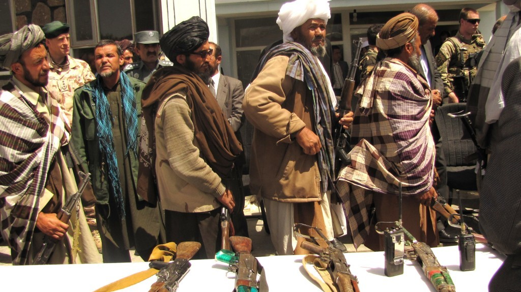 Illustrative photo of former Taliban fighters relinquishing their rifles to Afghan government officials in Ghor, Afghanistan, last May (photo credit: Joe Painter/US Department of Defense)