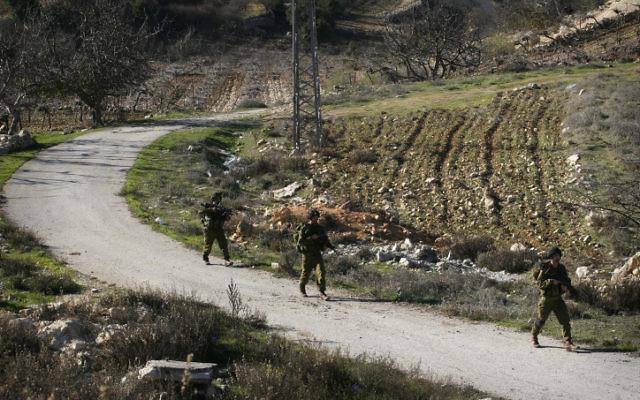 Des soldats de Tsahal patrouillent dans un champ situé près de Hébron. (Crédit : Michal Fattal/Flash90)