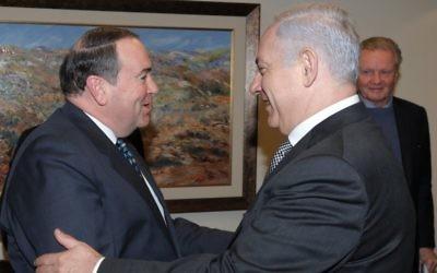 Mike Huckabee rencontre le Premier ministre Benjamin Netanyahu à Jérusalem, avec l'acteur Jon Voight en arrière plan, en 2011. (Crédit : Amos BenGershom/ GPO/Flash90)