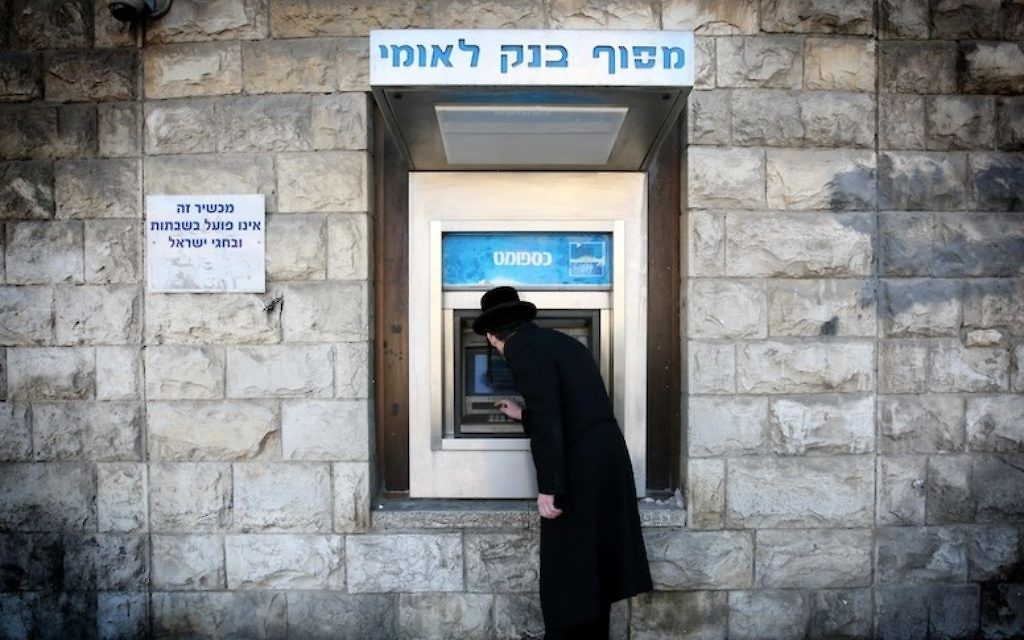 Un homme retire de l'argent d'un distributeur de la banque Leumi dans le quartier de Mea Shearim, à Jérusalem. Illustration. (Crédit : Nati Shohat/Flash90)