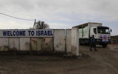 Les soldats de l'ONU regardent un camion de la Croix-rouge internationale chargé de pommes traverser le poste-frontière de Quneitra entre le plateau du Golan israélien et la Syrie en février 2011 (Crédit :  Tsafrir Abayov/Flash90)