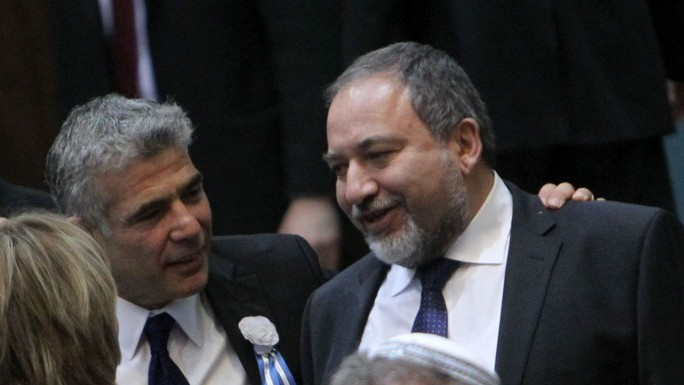 Yesh Atid party leader Yair Lapid seen with his hand on the shoulder of former foreign minister Avigdor Liberman during the opening session of Israel's 19th parliament, held at the Knesset, February 5 (photo credit: Miriam Alster/Flash90)