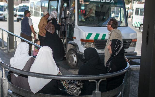 Des Palestiniens montent à bord d'un bus en direction de Ramallah vers la gare centrale des bus à Jérusalem Est (Crédit : Noam Moskowitz)