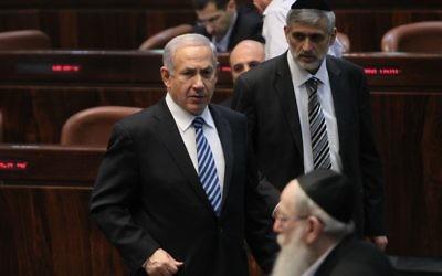 Benjamin Netanyahu avec Eli Yishai du Shas (au fond à droite) et Yaakov Litzman (arrière-plan) à la Knesset en 2013. (Crédit : Miriam Alster/Flash90)