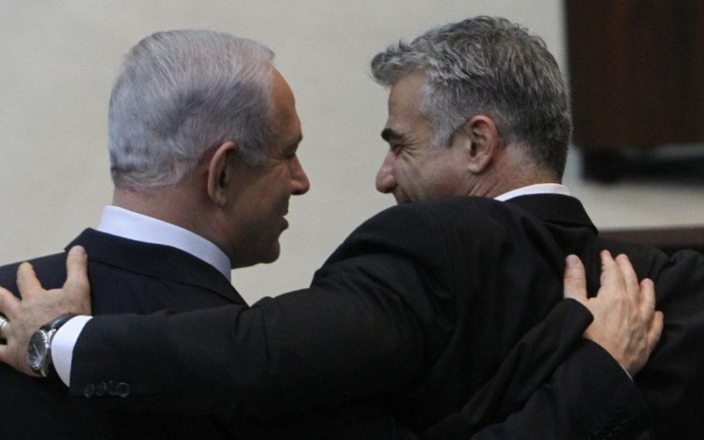 Le Premier ministre israélien Benjamin Netanyahu (à gauche) étreint le leader de Yesh Atid Yair Lapid après s'être adressé à la Knesset avant la prestation de serment du nouveau gouvernement, le 18 mars 2013. (Crédit : Miriam Alster/FLASH90/Fichier)