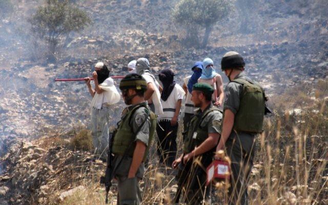 Des résidents masqués d'implantations se tiennent à côté de soldats de Tsahal en Cisjordanie (Crédit photo: Wagdi Ashtiyeh / Flash90)