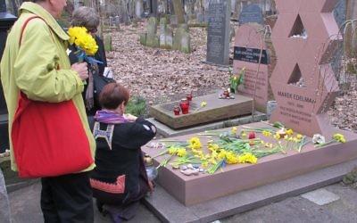 Des visiteurs placent des jonquilles sur la tombe de Marek Edelman, commandant du soulèvement du ghetto de Varsovie, dans le cimetière juif de Varsovie. (Ruth Ellen Gruber / JTA)