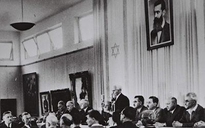 David Ben-Gurion, entouré des membres du gouvernement provisoire, proclame la Déclaration d'indépendance dans le hall du musée de Tel Aviv, le 14 mai 1948. (Crédit : bureau de presse du gouvernement israélien)