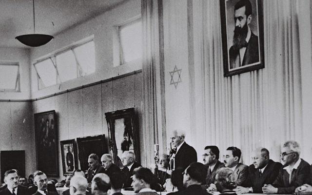 David Ben Gurion, entouré des membres du gouvernement provisoire, proclame la Déclaration d'indépendance dans le hall du musée de Tel Aviv, le 14 mai 1948 (Crédit : bureau de presse du gouvernement israélien)