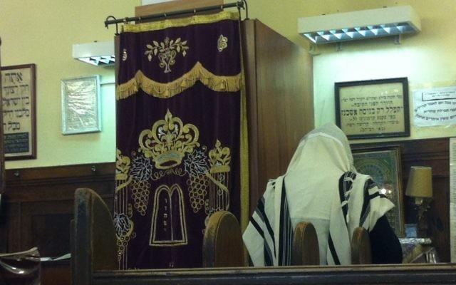 Un homme prie dans une synagogue. Illustration. (Crédit : Aaron Kalman)
