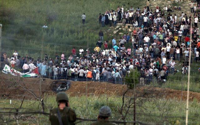 Des manifestants se réunissent le long de la frontière syrienne avec Israël avant de tenter de couper une ligne de fils barbelés et d'entrer sur le plateau du Golan israélien, une photo prise depuis le village druze de  Majdal Shams,   le 5 juin 2011 (Crédit : Flash90)