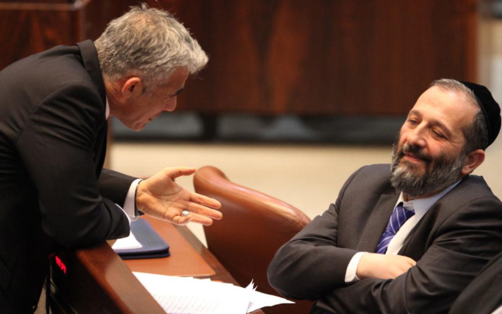 Le ministre des Finances de l'époque, Yair Lapid, (à gauche) s'entretient avec le président du Shas, Aryeh Deri, à la Knesset en mars 2013. (Isaac Harari/Flash90)
