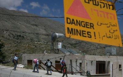 Des enfants druzes passent devant un panneau d'avertissement faisant état d'un champ de mines alors qu'ils rentrent d'une école à Majdal Shams sur le plateau du Golan (Crédit :  Lior Mizrahi / FLASH90)