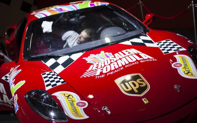 Un homme nettoie une voiture de course Ferrari qui va être présentée dans la Vieille Ville - juin 2013 (Crédit : Flash90)