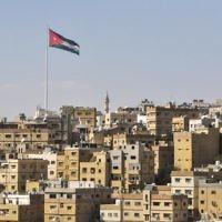 Vue d'Amman avec le drapeau jordanien flottant sur la ville. (Crédit : Michal Shmulovich/Times of Israel)