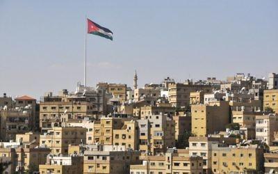 Vue d'Amman avec le drapeau jordanien flottant sur la ville (Crédit : Michal Shmulovich/Times of Israel)