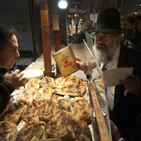 Un représentant du Grand Rabbinat inspecte un certificat de casheroute suspect dans un stand d'alimentation, Jérusalem, le 28 mars 2011. (Crédit : Rubin Salvadori/Flash90)