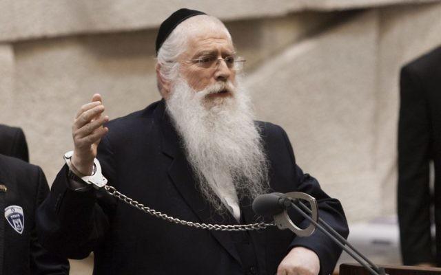 Le député Meir Porush (Yahadut Hatorah) s'est menotté au podium de la Knesset en juillet 2013 pour manifester contre le projet de loi de conscription des ultra-orthodoxes. Des centaines de milliers de haredim sont attendus lors d'une manifestation contre le projet, à Jérusalem, dimanche après-midi. (Crédit : Flash90)