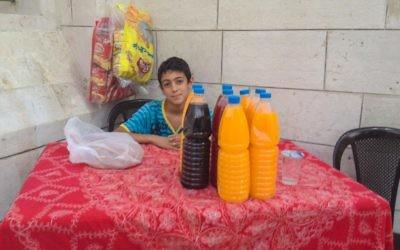Un jeune résident d'Amman qui installé un stand de jus à l'extérieur d'une mosquée pour que les gens puissent rompre le jeûne (Crédit t: Michal Shmulovich/Times of Israel)