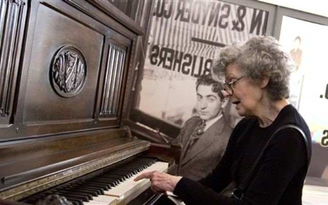 Linda Emmet, the daughter of musician Irving Berlin, plays on her father's piano at the Red Star Line museum in Antwerp, Belgium on Thursday, Sept. 26, 2013. (photo credit: AP Photo/Virginia Mayo)