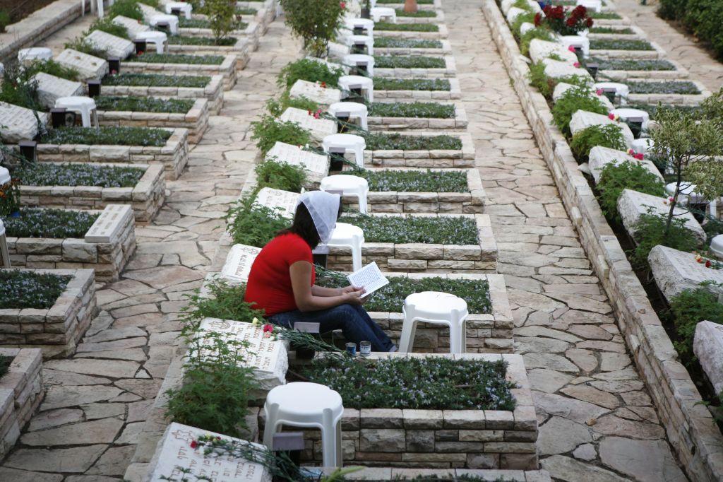 Une femme prie près de la tombe d'un soldat tombé au combat durant la guerre de Kippour en 1973, au cimetière militaire du mont Herzl. (Crédit : Michal Fattal/Flash90)