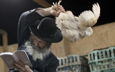 Un juif ultra-orthodoxe participant au rituel de  kapparot , pendant lequel un poulet est secoué au dessus de la tête, l'individu transférant par ce geste ses péchés au volatile. Illustration. (Crédit : Dima Vazinovich/Flash90)