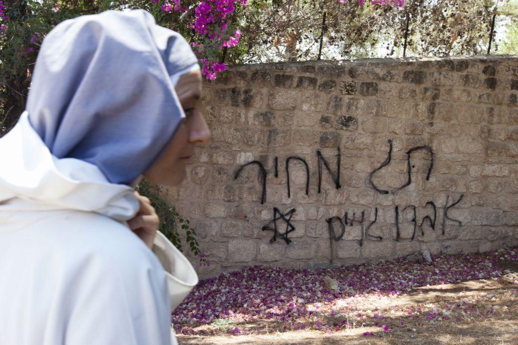 """Une nonne passe devant un graffiti """"prix à payer"""" dans une église située à proximité de Beit Shemesh. (Photo d'illustration : Flash90)"""