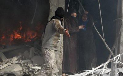 Des habitants dans les décombres d'un immeuble touché par une attaque aérienne de l'armée syrienne, le 30 janvier 2014 à Alep (Crédit: AFP/Mohammed al-Khatieb)