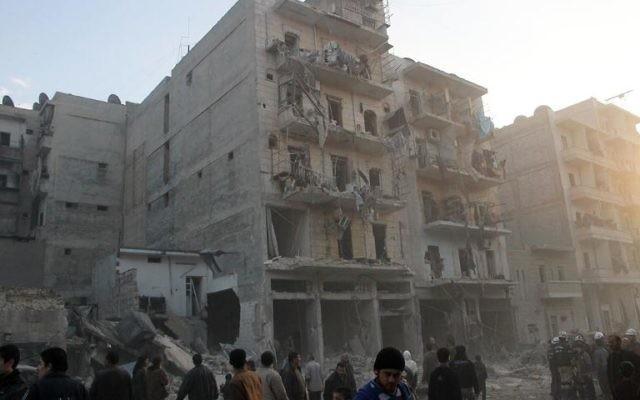 Des habitants devant un immeuble touché par une attaque aérienne de l'armée syrienne, le 29 janvier 2014 à Alep (Crédit : AFP/Mohammed Al-Khatieb)
