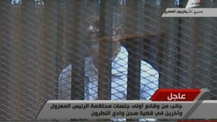 Capture d'image de la télévision égyptienne montrant le président déchu Mohamed Morsi derrière le grillage d'une cage pendant son procès, le 28 janvier 2014 au Caire  (Crédit : Télévision égyptienne/AFP)