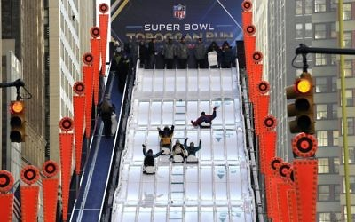 Des fans du Super Bowl glissent sur un tobogan géant à Manhattan, le 29 janvier 2014 (Crédit : AFP)