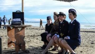 Des femmes en uniforme militaire de la deuxième guerre mondiale sur la plage d'Anzio en Italie pour rejouer le débarquement du 22 janvier 1944. (Crédit : AFP/Andreas Solaro)