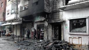 Des habitants dans une rue de Homs après des tirs au mortier de rebelles syriens, le 9 janvier 2014  (Crédit : Sana/AFP/Archives)