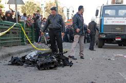 Des policiers et des habitants sur les lieux d'un attentat à la voiture piégée devant le quartier général de la police - 24 janvier 2014 (Crédit AFP/Khaled Kamel)