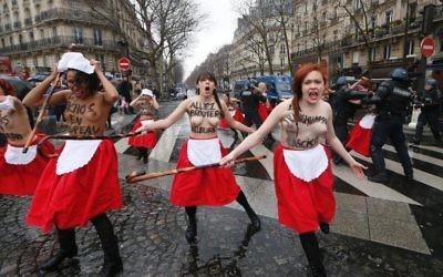 """En marge de la manifestation, une dizaine de militantes du groupe """"Femen"""" ont scandé """"allez brouter ailleurs"""", avant d'être arrêtées par les forces de l'ordre.  (Crédit : AFP/Thomas Samson)"""