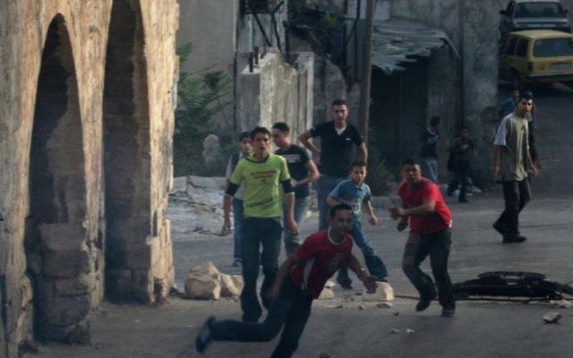 Des Palestiniens jettent des pierres en Cisjordanie (Crédit: Wagdi Ashtiyeh/Flash90)