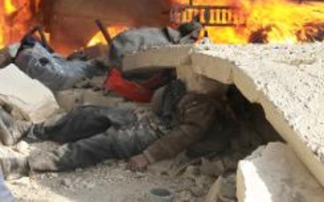 Le corps d'un homme coincé sous les gravats, sur le site d'une attaque à la bombe à Alep le 21 janvier 2014  (Crédit : AFP/Archives Mahmud Al-Halabi)