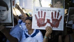 Manifestants israéliens protestant contre la libération de prisonniers palestiniens en août 2013. Il est écrit sur la pancarte : Formulaire de sortie de prison (Crédit  : Flash 90)