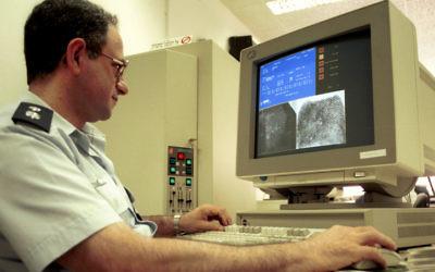 Un policier utilise un ordinateur pour identifier des empreintes (Crédit : Yossi Zamir/Flash90)