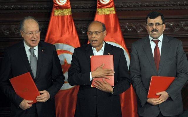 Le chef de l'Etat tunisien Moncef Marzouki (c), le Premier ministre sortant Ali Larayedh (d) et le président de la Constituante, Mustapha Ben Jaafar (g) posent avec des copies de la nouvelle constitution, lors d'une cérémonie à Tunis, le 27 janvier 2014  (Crédit : AFP/Fethi Belaid)